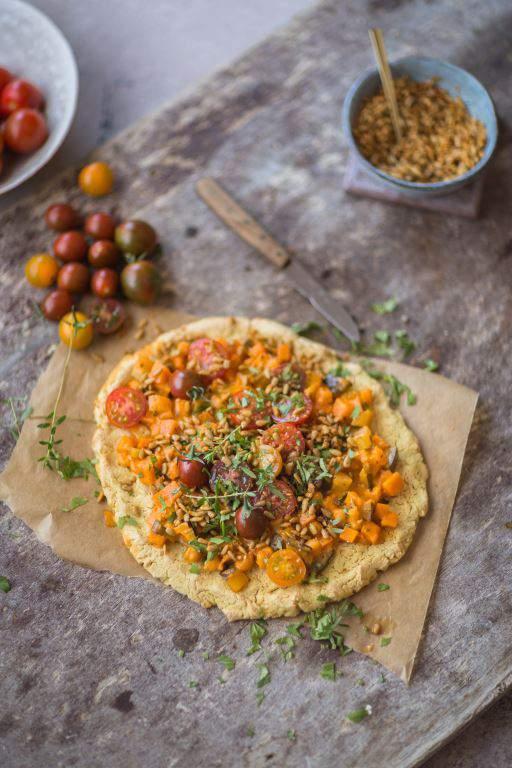 Glutenfreie Kichererbsen Pizza mit Gemüsetopping und Curry-Sonnenblumenkernen